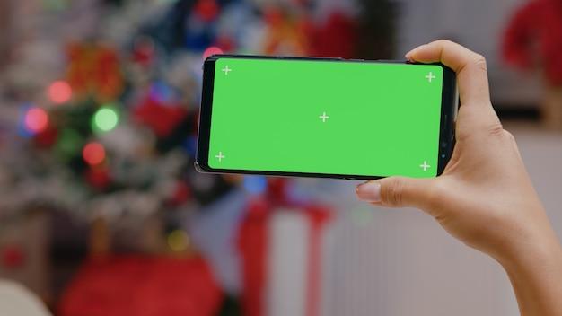 스마트폰에서 수평 녹색 화면을 들고 있는 손 클로즈업