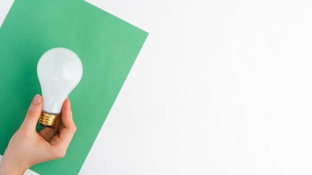 白い背景に、緑の紙の上に電球を持っている手のクローズアップ