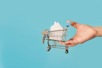 Close-up of hand holding miniature shopping cart with paper house and keys against blue background