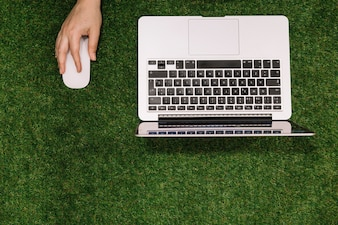 Close-up of hand holding mouse with open laptop on fake grass backdrop