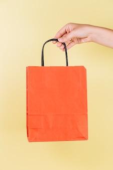 Крупным планом рука, холдинг бумажный мешок в руке на желтом фоне