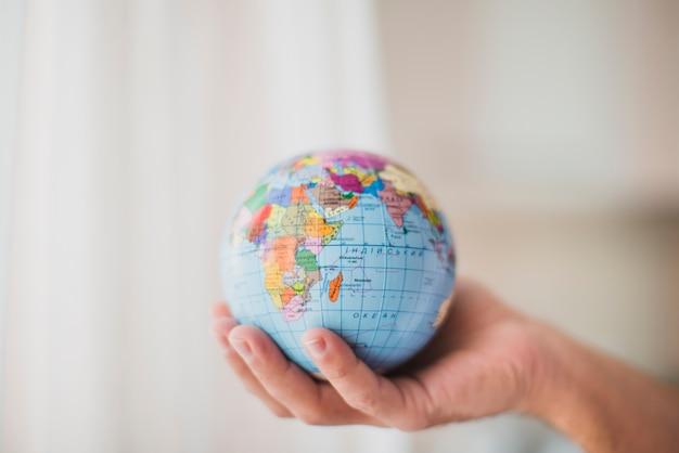 Крупным планом рука, холдинг небольшой глобус