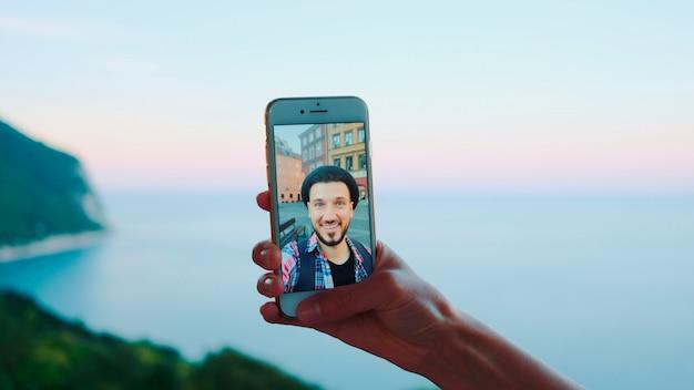 海の前で男性とのビデオ通話中にスマートフォンを持っている手のクローズアップ。背景の美しい風景。