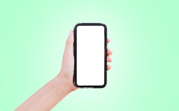 Крупный план руки, держащей смартфон с белым макетом, изолированным на пастельно-зеленом.
