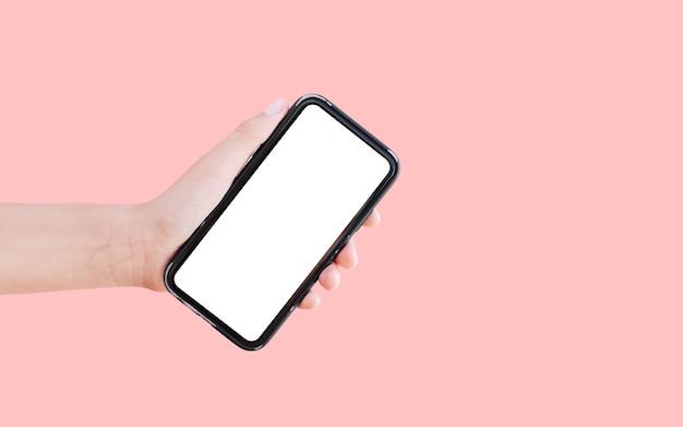 パステルピンクで隔離の白いモックアップとスマートフォンを持っている手のクローズアップ。