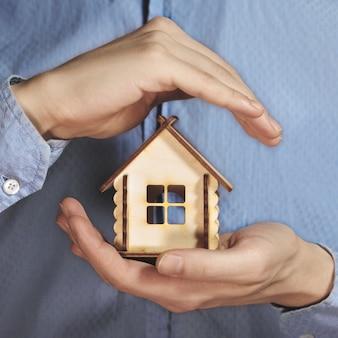 Крупным планом руки, держащей модель дома экономить маленький дом