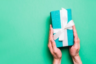 Close-up of hand holding wrapped gift box with white ribbon against green background