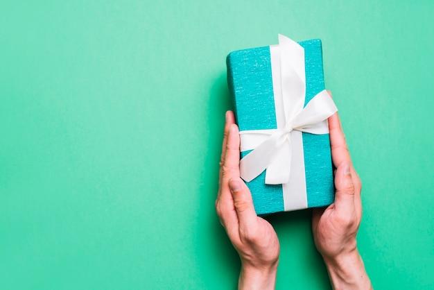 손을 잡고 근접 녹색 배경에 흰색 리본 선물 상자 포장