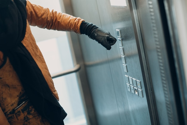 코로나바이러스 전염병 covid-19 검역 개념 동안 장갑 집게손가락으로 버튼 엘리베이터를 누르는 손 클로즈업