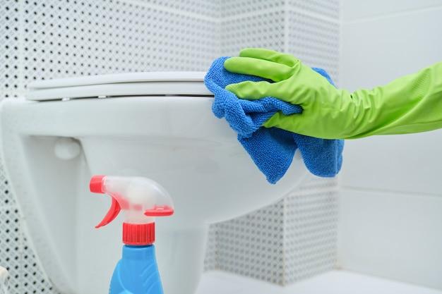 Крупный план руки в перчатках с тряпкой и моющим средством, висящим унитазом