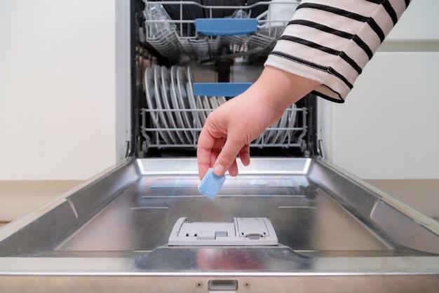 부엌에서 식기 세척기에 비누 캡슐을 삽입하는 손을 닫습니다.