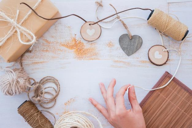 스풀 및 화이트 책상에 포장 된 선물 상자 하트 화환을 만드는 손의 근접