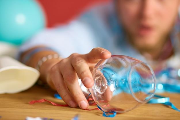 手のクローズアップ男はブランデーのグラスを持って、独身最後のパーティーの後に散らかった部屋のテーブルで寝て、家でパーティーの後に疲れた男