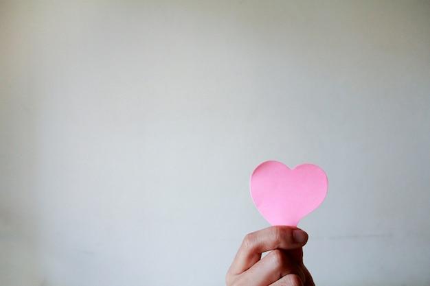 흰색 배경으로 종이 심장을 들고 손 남자의 닫습니다. 사랑 개념, 해피 발렌타인입니다.