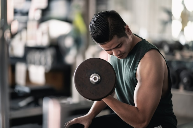 체육관, 스포츠 개념에서 아령 운동을 사용하여 손 남자의 닫습니다