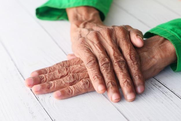 Крупным планом руки пожилого человека, изолированные на белом столе