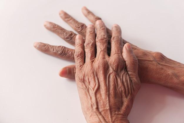 Крупным планом руки пожилого человека, изолированные на белом.