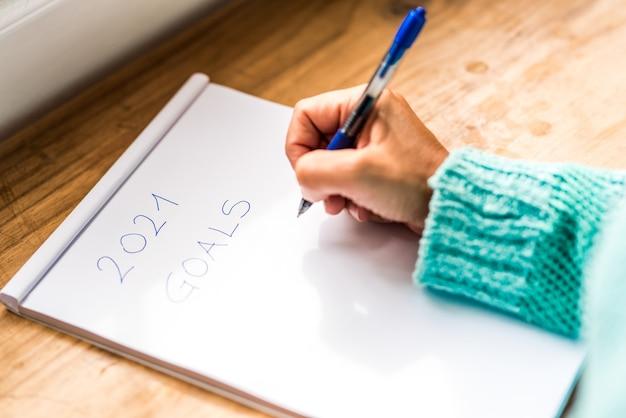 파란색 셔츠나 스웨터를 입은 여성의 손을 가까이서 펜으로 2021년 목표를 종이에 적습니다