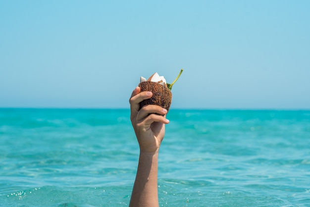 海と空に対してココナッツのスライスが入った半分のココナッツの殻を持っている認識できない人の手のクローズアップ。ココナッツの殻で夏に手を濡らします。海に対してココナッツを持って手を上げた