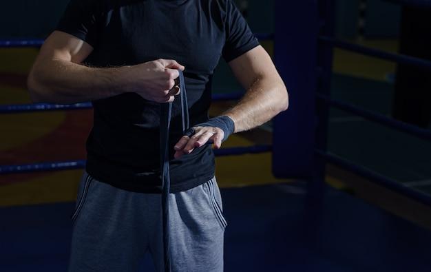 戦いやトレーニングの前に手首のラップを引っ張るボクサーの手のクローズアップ。 Premium写真
