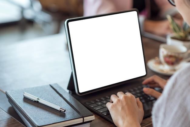 테이블에 흰색 화면에 디지털 태블릿을 사용하는 사업가의 손 클로즈업