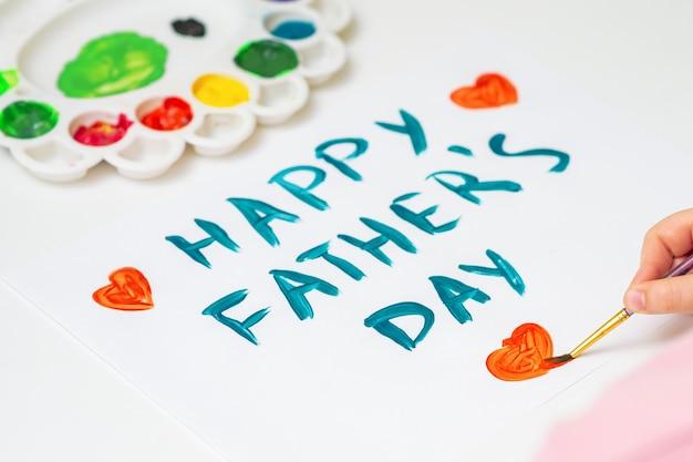 Закройте руки ребенка, рисующего красное сердце с текстом поздравительной открытки дня отца акварелями на белой бумаге. день отца и концепция семьи.