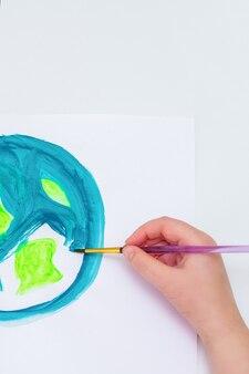 Закройте руки ребенка, рисующего изображение земного шара. ребенок рисует землю кистью акриловыми красками на белой бумаге. концепция дня земли. вид сверху.
