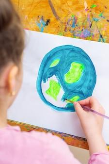 Закройте руки ребенка, рисующего изображение земного шара. ребенок рисует землю кистью акрилом на белой бумаге на мольберте. концепция дня земли.