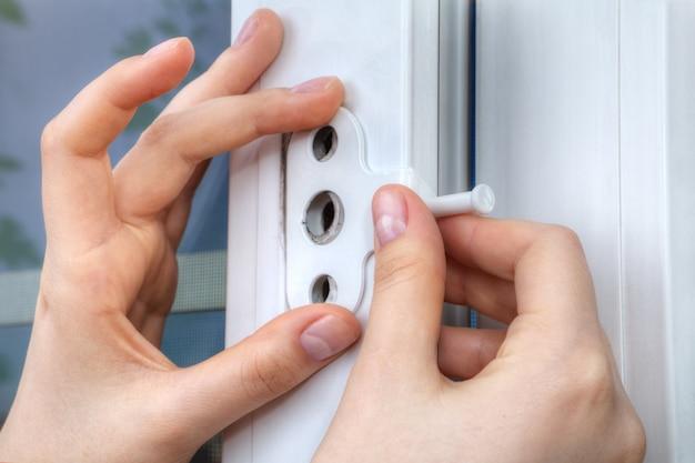 플라스틱 프레임에 창 리미터를 설치하는 자물쇠의 손 클로즈업.