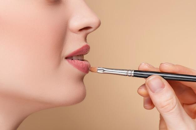 여성 입술에 립스틱을 적용하는 메이크업 아티스트의 손 클로즈업