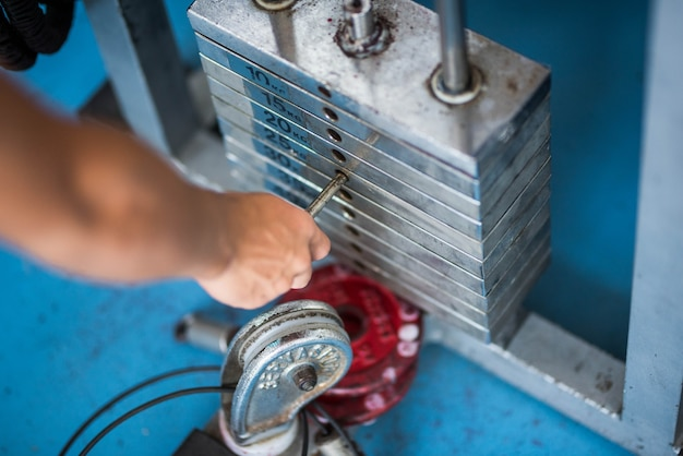 ジムのマシンで体重を変える男性または女性の手のクローズアップ-ウェイトリフティングの概念とボディービル