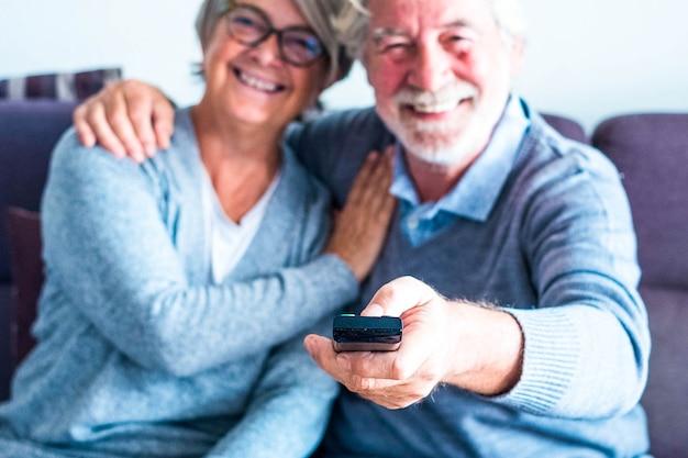 Крупным планом руки зрелого мужчины, держащего пульт дистанционного управления и переключающего канал или фильм в телевизоре - пара из двух пожилых людей дома на диване, глядя в камеру