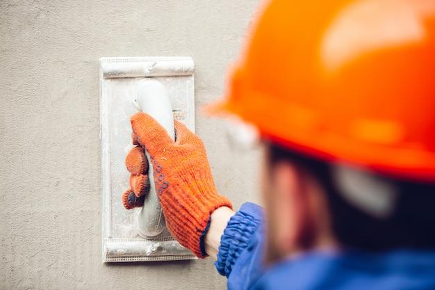 Закройте руки ремонтник, профессиональный строитель работает в помещении, ремонт