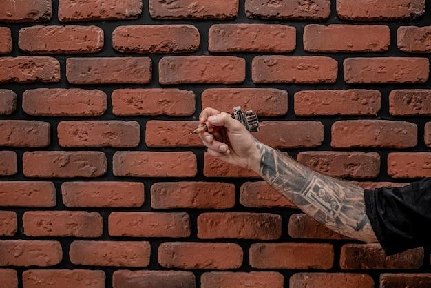 벽돌 배경에 문신 기계를 들고 손 구식 hipster 문신 예술가의 클로즈업.
