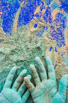 Close-up of hand painted with holi color powder on blue background