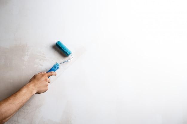 ローラーで手の絵画の壁のクローズアップ。