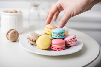 Close-up of hand picking up the colorful macaroons from white plate on the table
