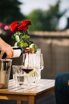 나무 테이블에 투명 유리에 와인을 붓는 손 클로즈업