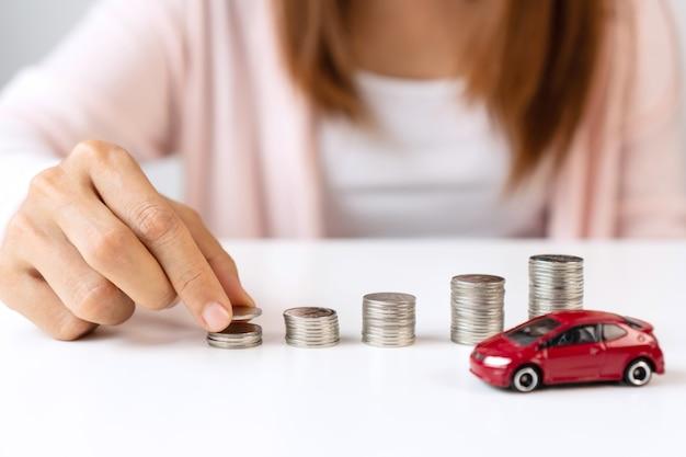 お金を節約するためにパイルコインにコインを置く手のクローズアップ。新しい車を買うためにお金を集めて、貯金と自動車ローンの概念。フラットレイ