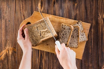 Close-up of hand's cutting the loaf of bread with knife on chopping board