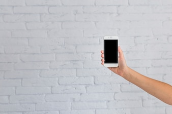 Close-up of hand showing mobile phone in front of white brick wall