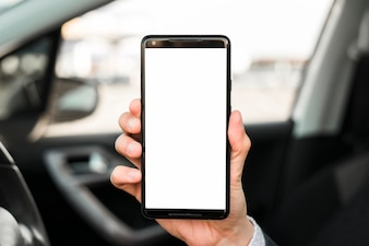 白い画面表示を持つ携帯電話を示す手のクローズアップ