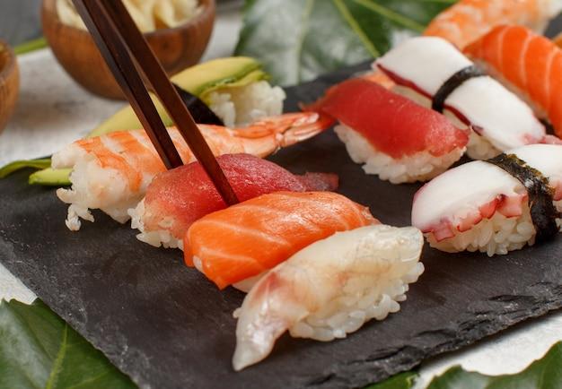 寿司バーの皿から箸でロールを取る手のクローズアップ