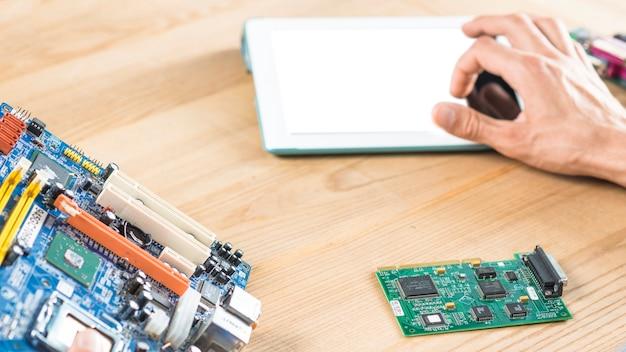 Крупный план руки касаясь цифровой планшет с материнской платой и цепи на деревянный стол