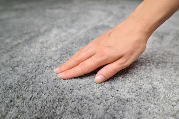 Крупный план руки, касающейся мягкого ковра нежный и пушистый ковер между пальцами