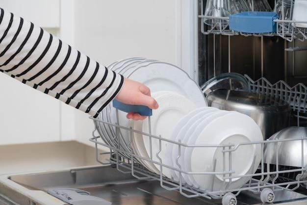부엌에서 손을 내리는 접시 세척기를 닫습니다. 식기 세척기의 전체 선반의 가전 제품을 가져가는 사람.