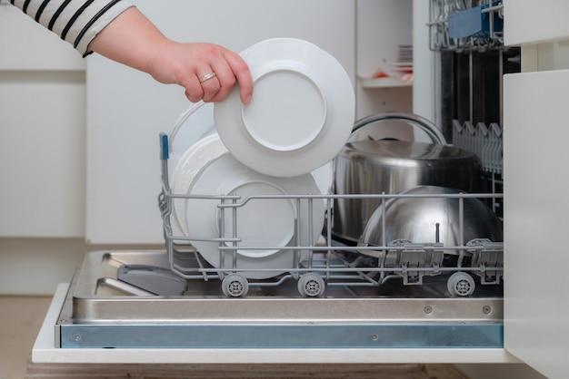 Крупным планом ручной разгрузки посудомоечной машины на кухне.