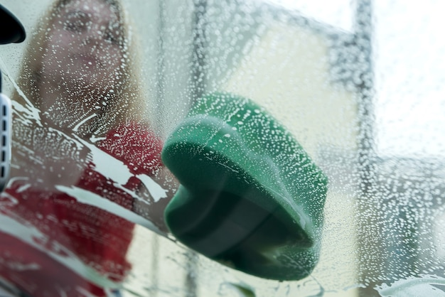 스폰지와 비누 거품으로 손을 씻는 차 클로즈업