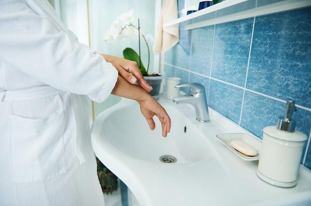 손 씻기의 클로즈업입니다. 와플 목욕 가운을 입은 여성이 욕실의 세면대 옆에 서서 손을 씻습니다