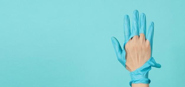 파란색과 녹색 또는 tiffany blue 색상 background.monotone coclor에 찢어진 의료용 장갑이나 찢어진 고무 장갑을 끼고 손을 닫습니다.
